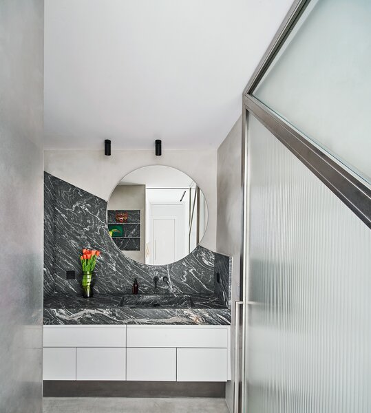 Black marble and shower glass angles in the bathroom to complete the triangle motif.