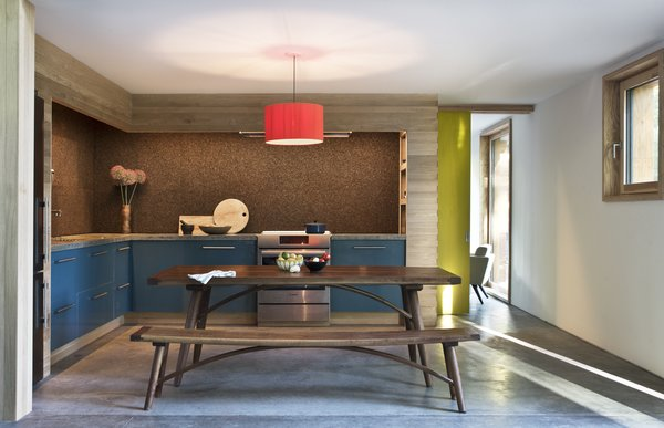 The kitchen is open to the living area, and the guest bedroom can be seen beyond. The picnic table is by Hudson Workshop, and the bright-red light fixture is by Santa & Cole.