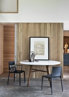 The white oak millwork finishes throughout the rooms are repurposed from ceiling slats to offer a warm counterpoint to the concrete slab floor. The dining table is by Hudson Workshop, and the matte black chairs are by Allermuir.