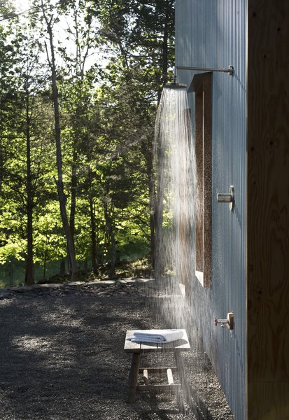 The secluded location of the house at the edge of a retired shale bank allows the luxury of an open outdoor shower. Corrugated steel siding provides a durable, zero-maintenance exterior finish and captures the changing sun and woodland shadows.