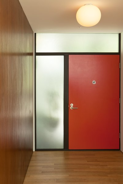 A view of the entry from inside. A mid-century palette and simple modern graphic of warm walnut, textured glass, painted door, and stained wood door jambs.