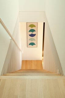 A new staircase connects the upstairs to what was formerly more of a recreational basement/ lower floor.  The stair is positioned to best allow our clients to walk from the kitchen/dining area downstairs, where new sliding glass doors lead to the pool area.