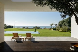 """The """"leisure zone"""" of Sea Front Villa naturally frames the sea. An infinity pool embedded in the lawn further blurs the line between the house and its surroundings."""