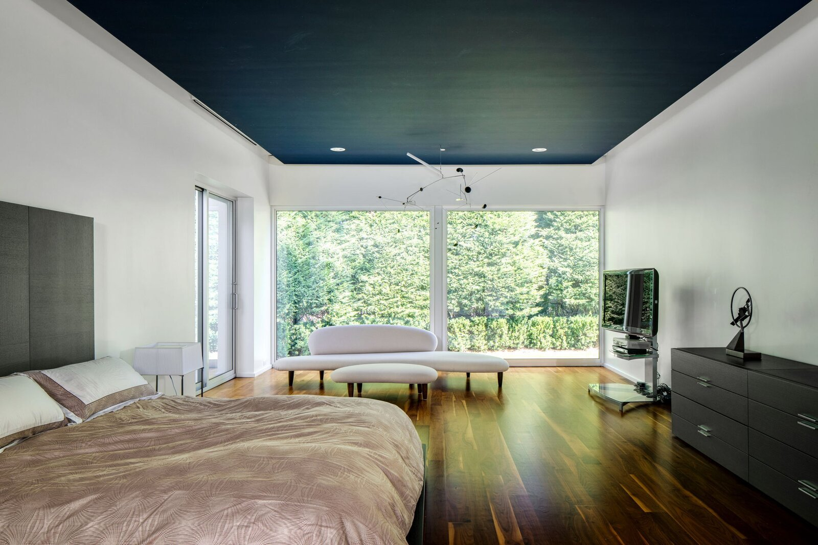 Bedroom, Bench, Bed, Ceiling Lighting, Storage, Dark Hardwood Floor, and Dresser The main bedroom occupies Harrison's former studio.  Photo 7 of 10 in After a Herculean Renovation, Architect Wallace Harrison's Landmarked Home Seeks a New Caretaker