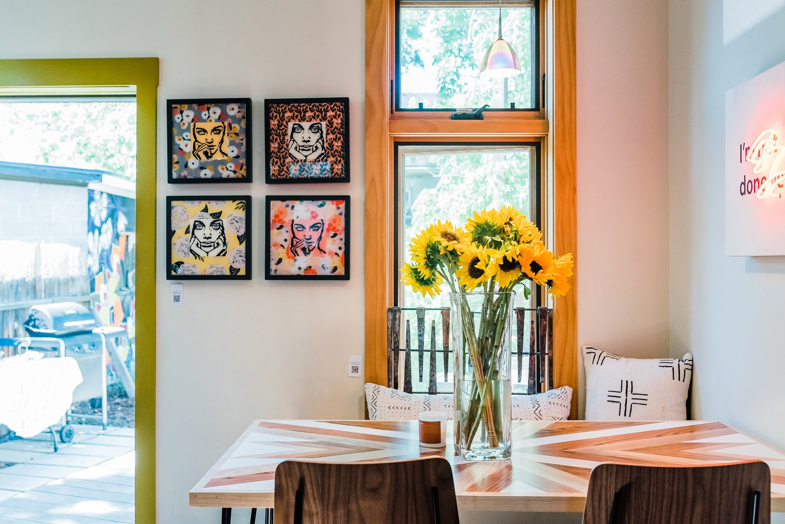 Dining Room A view to the backyard at The Sursy GandyHouse.  Meet The Makers: PILLOWS / Olive & Olde's (Denver, CO) TABLE / The Sursy Collection x Protea & Pine (Denver, CO) NEON ART / Scott Young (Denver, CO) 'FACES' COLLECTION / WCB Designs (Nashville, TN)  The Sursy GandyHouse by The Sursy from The Sursy WeeHouse