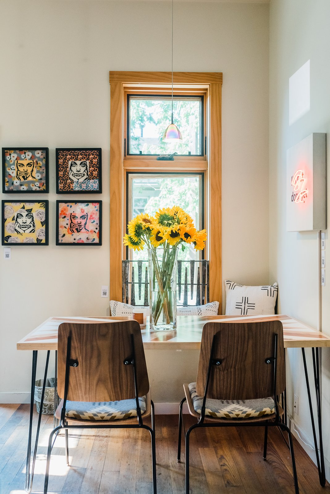 Dining Room, Medium Hardwood Floor, Bench, Table, Chair, Accent Lighting, Wall Lighting, and Storage Intimate + quirky dining nook in The Sursy GandyHouse! Everything is shoppable.  Meet The Makers: 'THE CARSON' SIDE CHAIRS / Onefortythree (Henderson, NV) 'THE SURSY' TABLE / Protea & Pine (Denver, CO) 'NOT DONE YET' NEON ART / Scott Young (Denver, CO) PILLOWS / Olive & Olde's (Denver, CO) 'FACES' COLLECTION / WCB Designs (Nashville, TN)  The Sursy GandyHouse by The Sursy