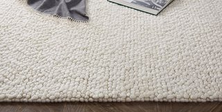 Wool loops of varying thickness form the pebble-like ground of Ria rug.