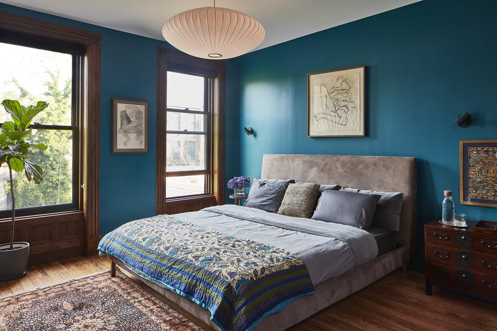 Bedroom, Dresser, Ceiling Lighting, Bed, Medium Hardwood Floor, Pendant Lighting, and Night Stands SECOND FLOOR - MASTER BEDROOM Photo © Ashok Sinha  Photos from Bed-Stuy Townhouse