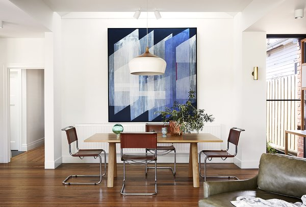 """""""We played with the ceiling forms to create spaces within the overall space, while soft natural light is introduced into the depths of the home with skylights,"""" says Lisa Breeze. The dining room of Coburg House takes advantage of this to stunning effect."""
