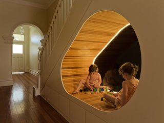 A uniquely shaped, well-lit nook under the stairs of the Peas in a Pod residence provides an imaginative space for play. CplusC Architectural Workshop designed much of the space around the clients four children's needs.