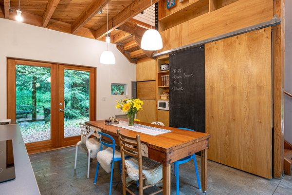 The long kitchen table, which can comfortably sit eight, has been handcrafted from salvaged cedar. Birch and chalkboard barn doors effortlessly hide any unwanted clutter.