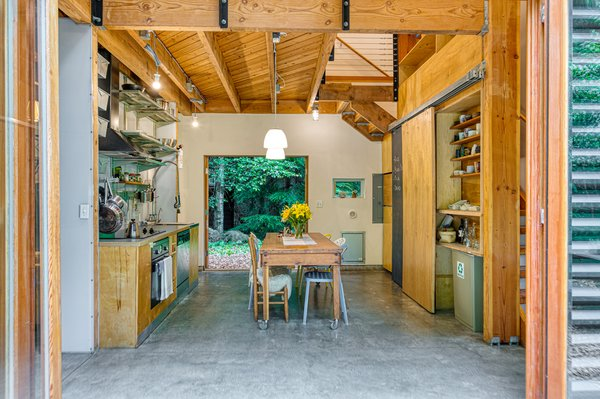 Expansive doors open the the kitchen up to the forest on two sides.