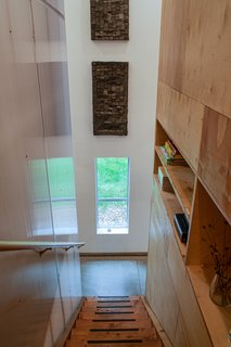 A fir beam stairway leads to the second floor. Open shelving provides additional storage.