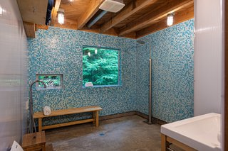 Speckled blue floor-to-ceiling tiles line the spacious bathroom shower, which also includes polished concrete and richly textured wood ceilings.