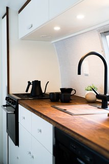 The kitchenette is an exercise in space efficiency; a handmade walnut insert covers the sink to maximize counter space.