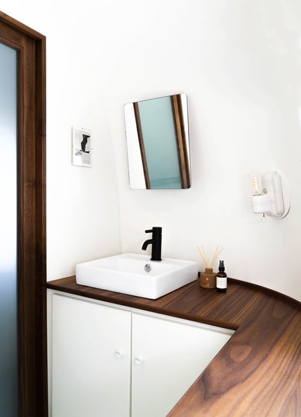 The minimalist bathroom features another walnut countertop. The Airstream's curves and lack of straight walls presented a challenge for August, who built all of his own cabinetry.