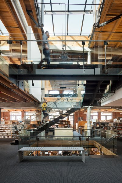 Renowned architecture firm Olson Kundig occupies three floors of a 19th-century loft building in Seattle's historic Pioneer Square neighborhood. A crucial concern was opening the office up to more natural light; a staircase that cuts through the office's three levels was added underneath the central skylight, which opens via a hydraulic lift system.