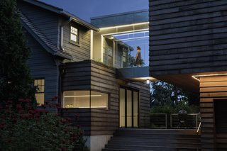 A patio between the two structures serves as the house's primary entrance, and a place to hang out and grill. Architectural lighting in the walkway and above the garage reinforce the addition's geometric lines.