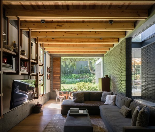 Exposed wooden rafters and hardwood floors add a softer touch to a space defined by hard materials and straight lines.
