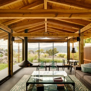The house's glassed-in living room provides plenty of scenery. The hanging fireplace and exposed rafters add a sense of lightness as well.