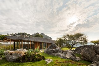 On a hill overlooking Lake Avándaro in Valle de Bravo—a popular weekend retreat about two hours west of Mexico City—lies the low-slung CMV House by Estudio MMX. The terrain around the lake is steep, rocky, and verdant, abounding with water-carved cliffs and boulders. The home's site, in particular, boasts vast views of the lake and the dramatic mountains that surround it.