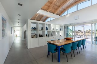 The dining room is separated from the living area by a built-in cabinet, both rooms are located under the home's airy vaulted ceiling.