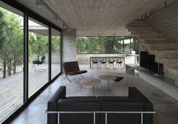 The home's interior is minimal and streamlined, with classic modern furnishings and polished concrete floors.