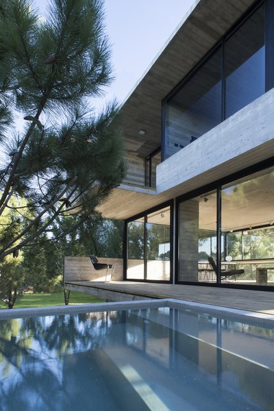 A swimming pool extends from the edge of the elevated terrace.