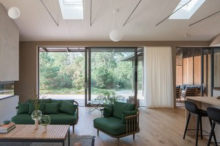 All of the fixed furniture is designed by Sundberg and made of oak. The clients worked with a local designer on the custom furniture, like the green sofa and chair in the living room. While the trees surrounding the property offer a decent amount of privacy, billowy white curtains add an additional layer.