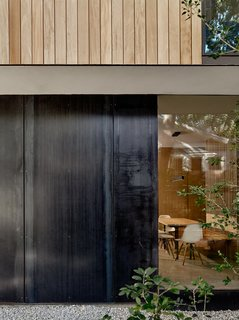 The exterior of the lower level is clad in mill-finished black steel panels, while the upper level features vertical Garapa wood siding.