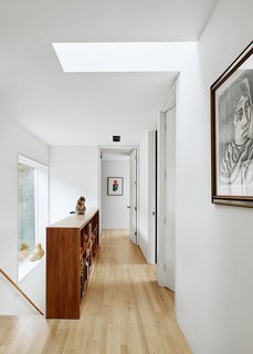 """The architects did not want """"the operating theater"""" of can lights, so Ernesto designed a custom fixture consisting of a simple steel plate that disguises """"cheap can lights,"""" seen here in the upper hallway.  """"It looks like a $1,500 fixture, but it's like $300,"""" he says."""