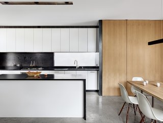 The kitchen features Ikea cabinets, soapstone countertops, and steel backsplash. The oak panel doors conceal additional storage and mechanicals.