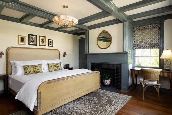 Guest rooms feature bespoke millwork, made with Colombian oak with raffia detailing. Vintage rugs come from Revival Rugs, textiles are Naturtex Espana, and the bedside sconce shades feature a flora print fabric from House of Hackney.