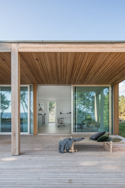 The sea-facing side has a large covered deck. Thin slats of larch on this facade create a slimmer profile that contrasts the large floor-to-ceiling windows.