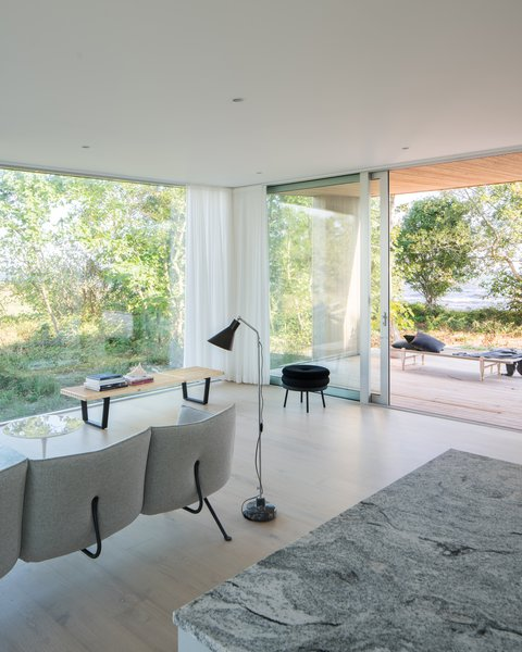 Inside, floor-to-ceiling windows and a clean white and wood palette make the landscape a focal point.