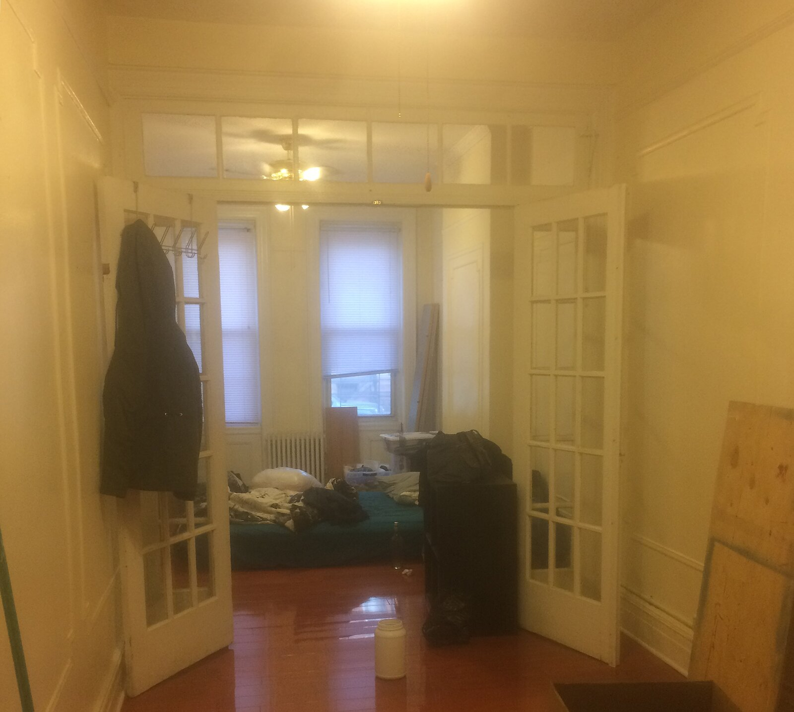 Before: Looking from the middle room into the bedroom. The railroad-style apartment had been painted a yellow-ish linen hue, and the hinges of the transom window above the bedroom doors were caked in decades of paint.  Photo 2 of 11 in Rental Revamp: An Architect Couple Reimagine a Dated Queens Apartment for Just $5K