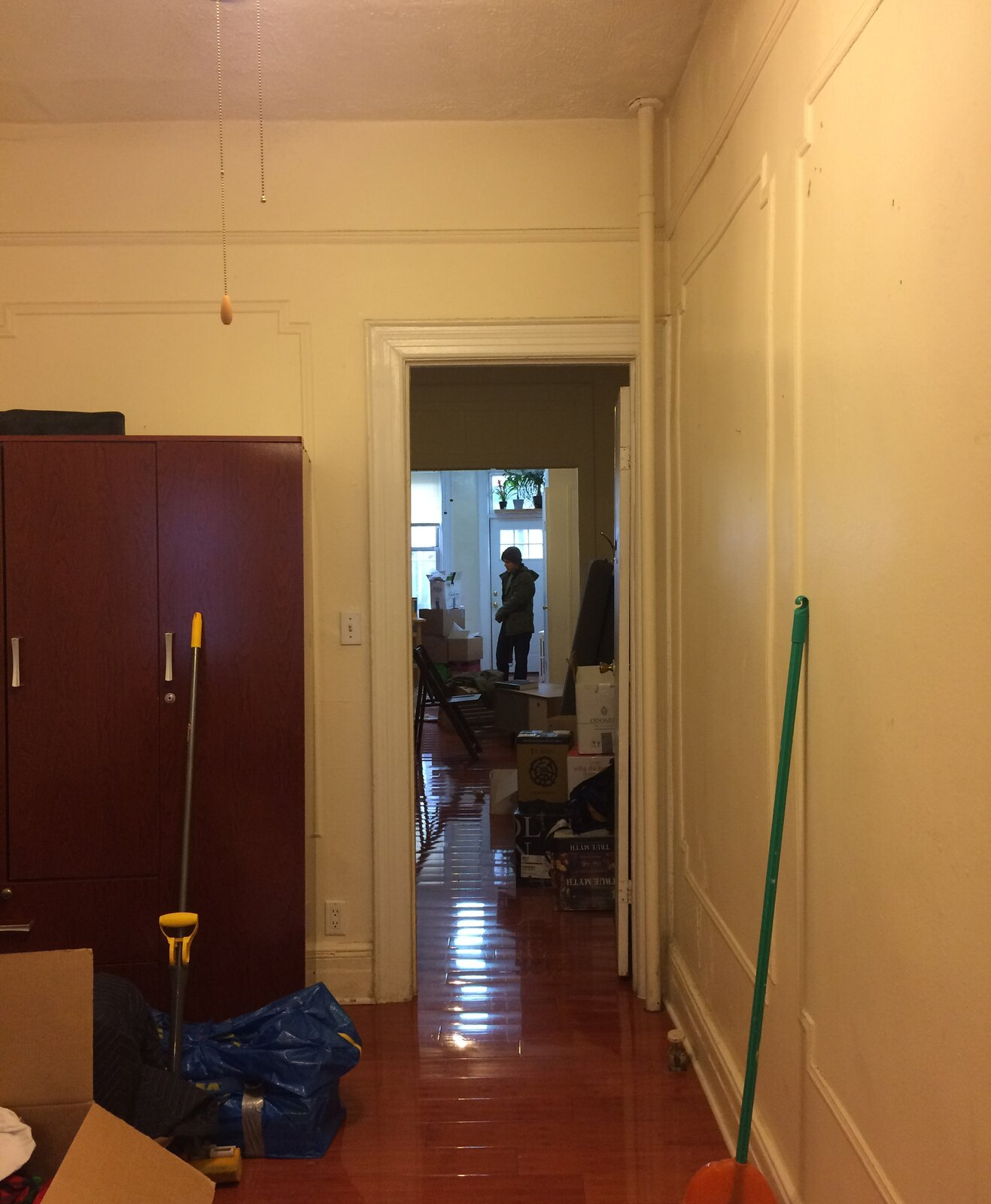 "Before: A middle room connecting the living room and bedroom previously had a ""saloon-style"" door that was too short, and a cheap, deep-red freestanding wardrobe.  Photo 6 of 11 in Rental Revamp: An Architect Couple Reimagine a Dated Queens Apartment for Just $5K"