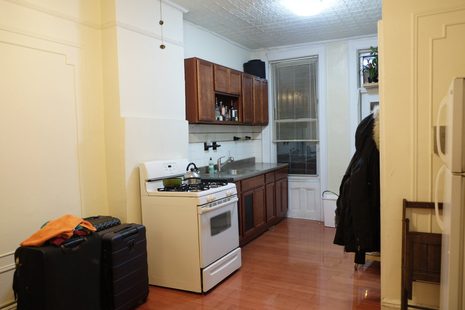 Before: The kitchen had minimal counter space, a fluorescent ceiling light, and a range with no workspace around it.    Photo 10 of 11 in Rental Revamp: An Architect Couple Reimagine a Dated Queens Apartment for Just $5K