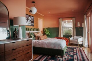 """An unusual pairing of pink and deep green find a happy match in this renovated apartment, which was DIY'ed by the homeowner, comedian Mamrie Hart, and her friend Claire Thomas, a creative director. """"I am used to painting,"""" says Thomas, """"but I was not emotionally prepared for the amount of trim in the bedroom."""" Cedarville, a pastel pink hue, and Green Bayou, both by Dunn-Edwards Paints, now cheer up the space."""