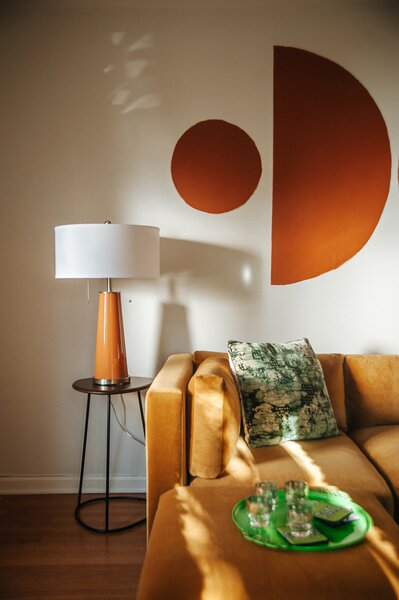 "The velvet marigold sofa from Joybird is a favorite addition. ""The ottomans aren't attached, so we can move them if my boyfriend and I don't want to sit next to each other, or we can make it a full bed,"" says Mamrie. The table lamp from Lamps Plus is the same Burnt Almond color as the mural."