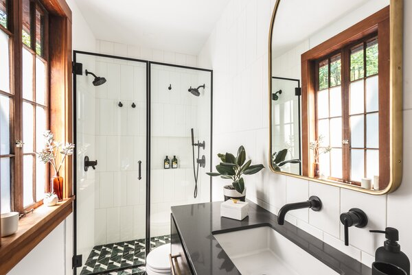 """After: The bathroom was divided into a powder room and primary bath, which features Ann Sacks tile in a geometric Kelly Wearstler pattern on the floor. """"I'm not one to put tile in a niche,"""