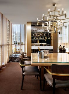 Kravitz Design's Bisha Suite at Bisha Hotel & Residences in Toronto features a gold-tone dining room and in-suite bar. A jewel-like, geometric chandelier hangs over the table.