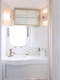 To create a sense of design continuity from the kitchen and living room, the same champagne-bronze hardware is featured in the bathroom.