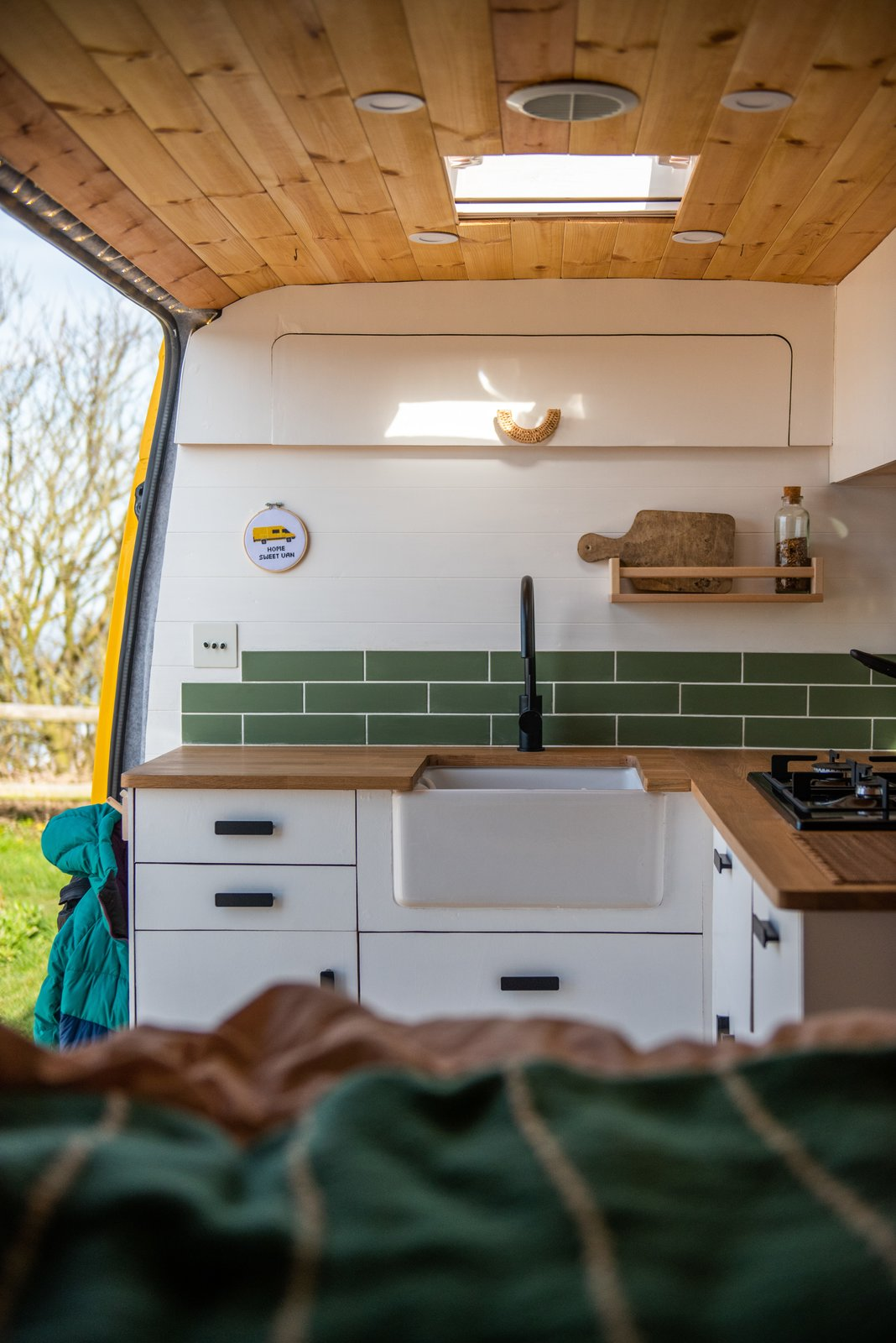 A Belfast sink adds a farmhouse feel to the polished kitchen.   Photo 16 of 22 in Budget Breakdown: A Climbing Couple Turn a Delivery Van Into an Adventure Mobile for $8.5K