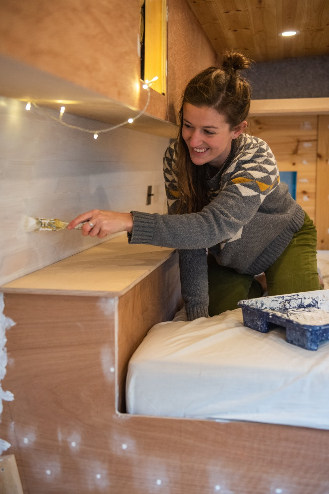 White paint complements natural wood and gives the space a fresh, Scandinavian-inspired vibe.  Photo 14 of 22 in Budget Breakdown: A Climbing Couple Turn a Delivery Van Into an Adventure Mobile for $8.5K