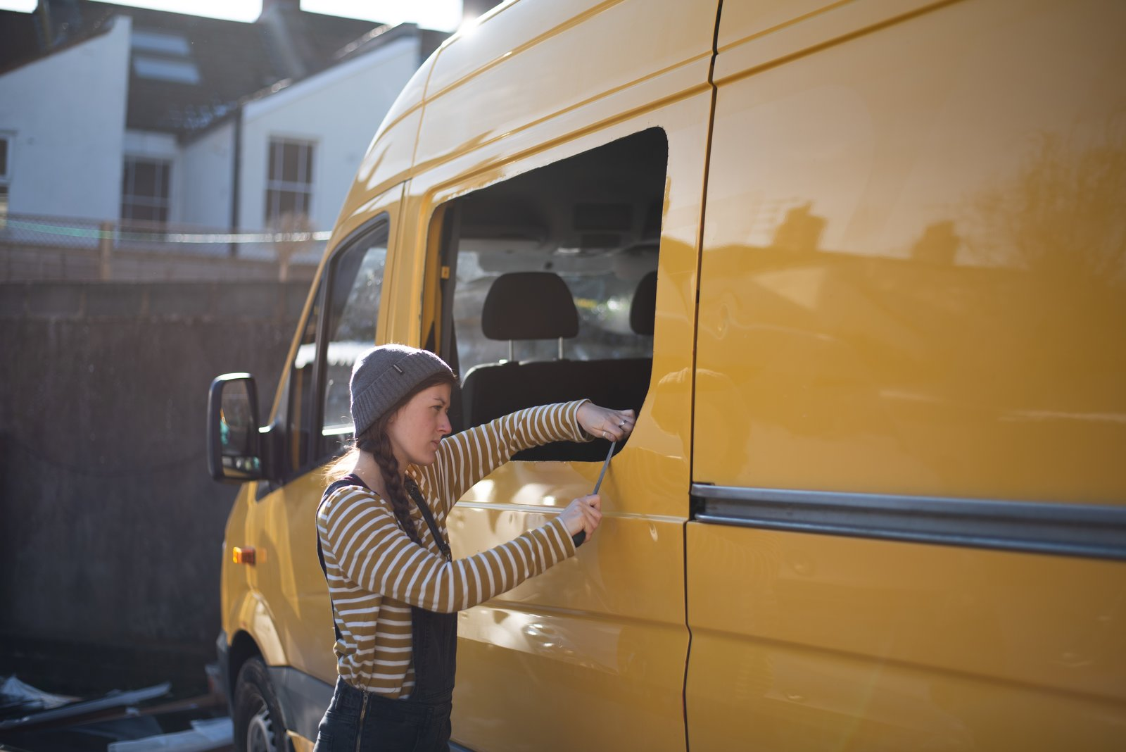 Charlie files away the rough edges of the new window opening.   Photo 7 of 22 in Budget Breakdown: A Climbing Couple Turn a Delivery Van Into an Adventure Mobile for $8.5K