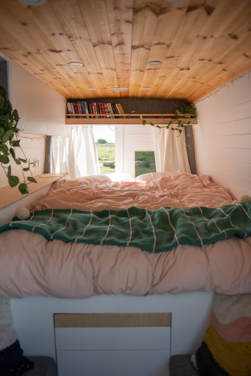 A bookshelf above the bed also holds space for greenery.  Photo 20 of 22 in Budget Breakdown: A Climbing Couple Turn a Delivery Van Into an Adventure Mobile for $8.5K