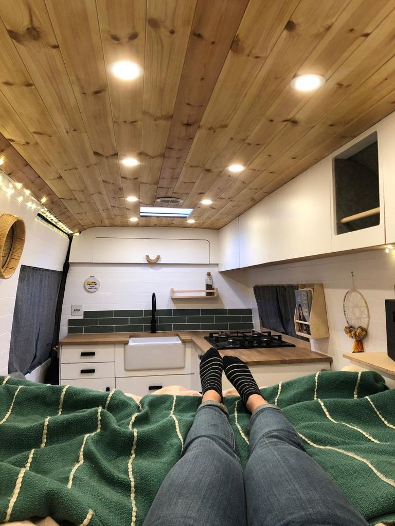 White cabinets, wood, and green tiles create a cohesive palette.  Photo 18 of 22 in Budget Breakdown: A Climbing Couple Turn a Delivery Van Into an Adventure Mobile for $8.5K