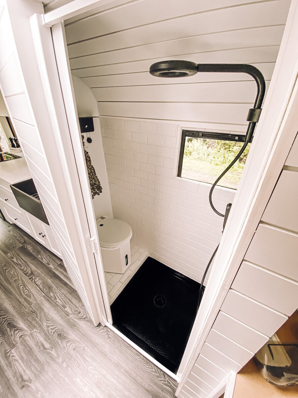 Buster the Bus black-and-white bathroom with composting toilet and matte-black showerhead