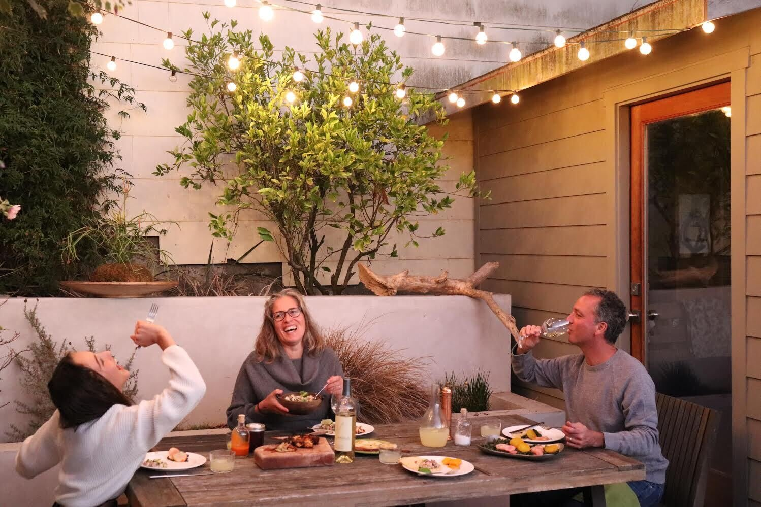 For principal and cofounder of Red Dot Studio Karen Curtiss, backyard dinners have become an important part of the family routine. She shares a silly moment with her daughter, Karen, and her husband, Mark.   Photo 8 of 10 in 10 Designers and Architects Share What They're Most Thankful for in a Turbulent Year
